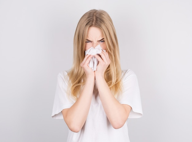 Studio portrait of cute unhealthy caucasian woman with paper napkin sneezing due to allergy