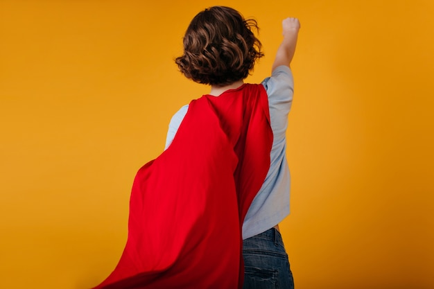 Studio portrait of dark-haired woman wears superhero mantle