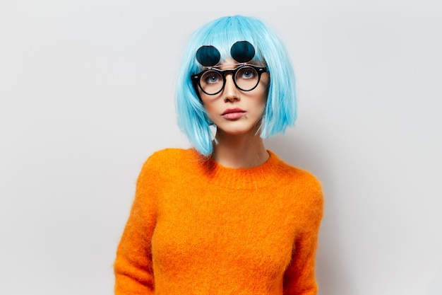 Studio portrait of fashionable pretty girl with bob hairstyle, wearing round hipster sunglasses and orange sweater on white background.