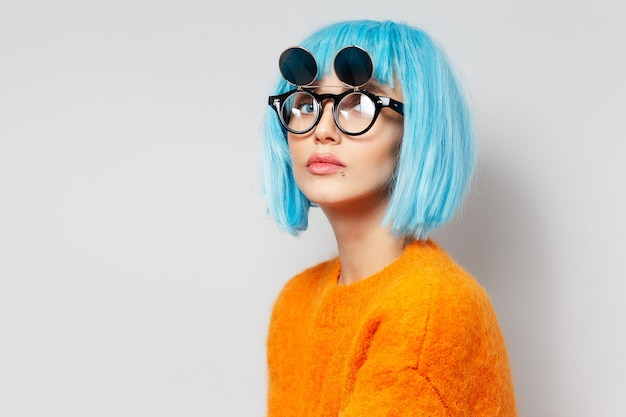 Studio portrait of fashionable young woman with blue hair bob in orange sweater against white background. wearing round hipster sunglasses.