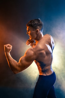 Studio portrait of fighting muscular man in smoke