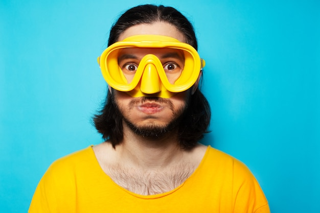 Studio portrait of funny diving man in yellow, on blue background.