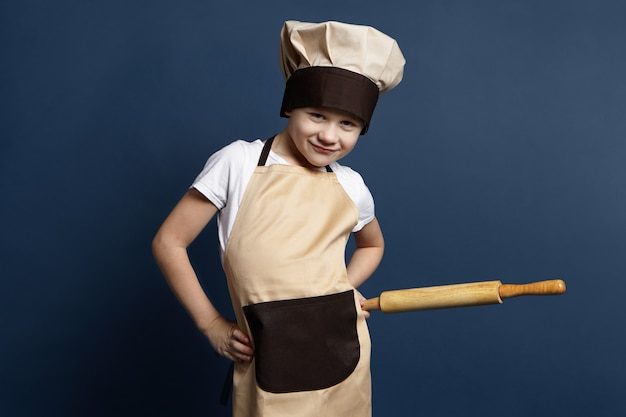 Studio portrait of funny playful little boy chef in apron and cap holding rolling pin, going to knead dough for homemade pizza or lasagne. cute male kid posing at blank wall with kitchen utensil