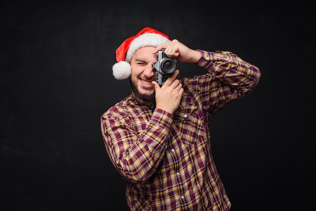 Studio portrait of funny and surprised bearded man wearing santa hat holding a retro camera, making a photo. space for text. black