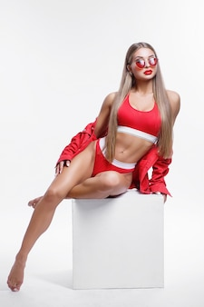 Studio portrait of a girl with a sport body in red clothes and sunglasses on a white background