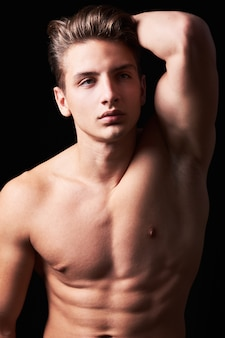 Studio portrait of handsome muscular shirtless young man isolated on black