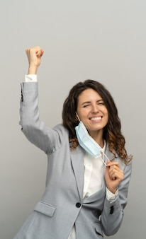 Studio portrait of happy business woman taking off mask, raising fist, grey background. female removing medical mask from face and looking at camera. coronavirus, covid-19 ended. pandemic is over.