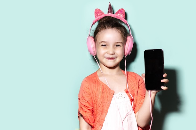 Studio portrait of happy child girl in coral shirt, holding smartphone, using pink headphones on background of aqua menthe color.