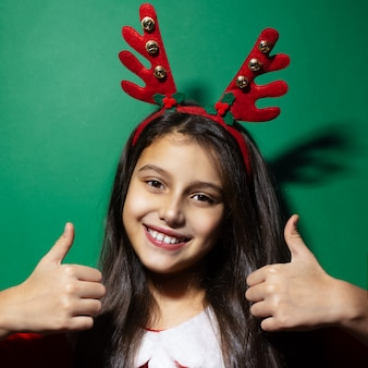 Studio portrait of happy child girl wearing reindeer horns and santa costume showing thumbs up on green