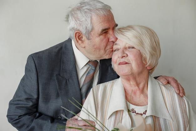 Studio portrait of happy elderly couple embracing against grey wall.