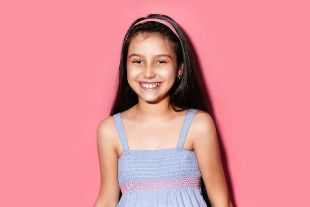 Studio portrait of happy little brunette child girl on background of pastel pink color. wearing blue dress and headband.