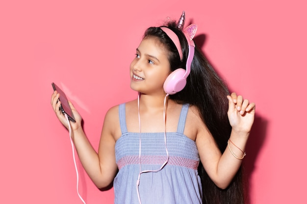 Studio portrait of happy little child girl, dancing and listening the music with headphones, holding smartphone