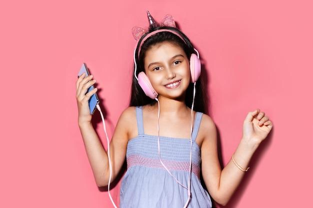 Studio portrait of happy little child girl, holding smartphone in hands, using headphones