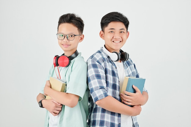 Studio portrait of happy schoolboys with headphones standing with students books and smiling