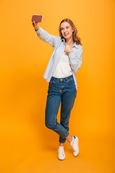 Studio portrait of happy woman wearing jeans and sneakers smiling and showing thumb up while taking selfie with cell phone, isolated over yellow space