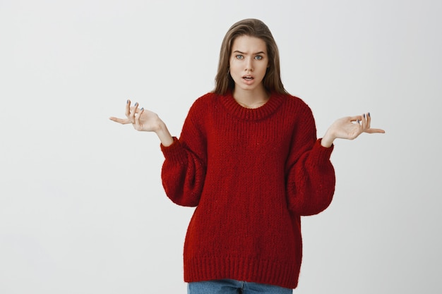 Studio portrait of intense angry european woman in trendy loose sweater, pointing sideways with displeased face, being bothered and angry during quarrel, standing