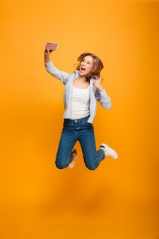 Studio portrait of joyful woman wearing jeans and sneakers smiling and showing thumb up while taking selfie with cell phone, isolated over yellow space