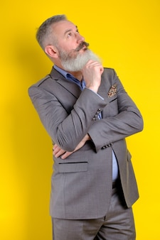Studio portrait mature bearded man dressed in gray business suit looks pensively aside, thinks about something, yellow background
