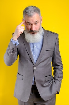 フォアフィンガー、素晴らしいアイデアや思考の概念、良い記憶、黄色の背景で頭を指す灰色のスーツに身を包んだスタジオポートレート成熟したビジネスマン。
