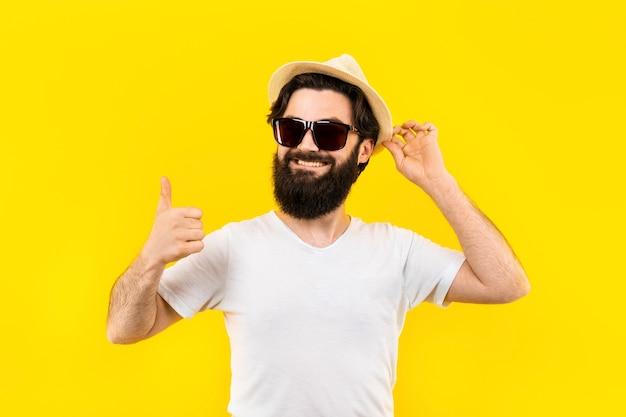 Tシャツとサングラスのひげを生やした男のスタジオポートレートは笑顔で次のように表示されます