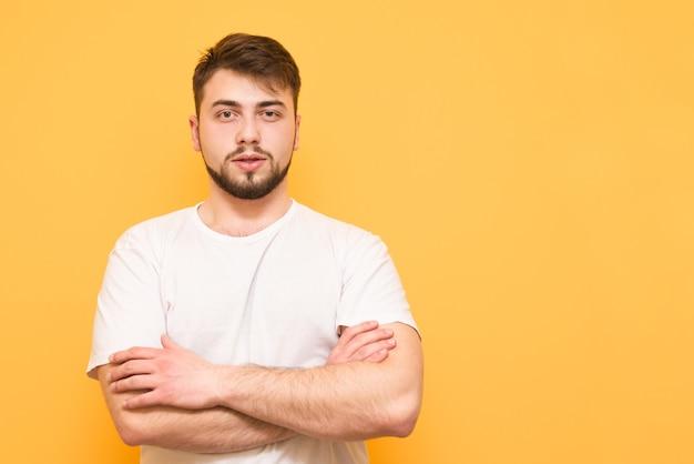 Студийный портрет бородатого подростка в белой футболке, стоящего на желтом