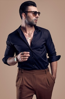 黒のシャツとメガネで美しい残忍な日焼けしたヒップスターの男のスタジオポートレート