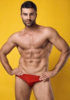 노란색에 빨간 속옷을 입고 아름다운 잔인한 검게 그을린 근육질 남자의 스튜디오 초상화