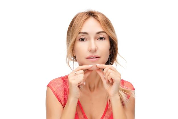 Студийный портрет красивой женщины кавказа без макияжа, касаясь ее кожи. концепция пластической хирургии. концепция красоты. концепция ухода за кожей. изолировать на белом.