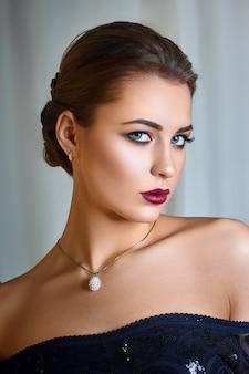 Студийный портрет красивой молодой женщины с каштановыми волосами.