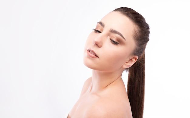 茶色の髪の美しい若い女性のスタジオポートレート