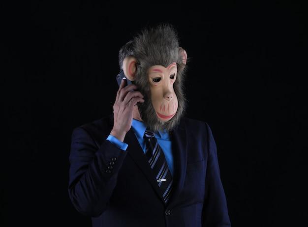 Студийный портрет бизнесмена в маске обезьяны