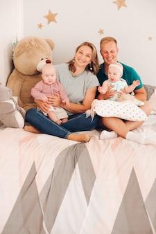 ベッドに座っている2人の幼児と陽気な家族のスタジオポートレート。ぬいぐるみと居心地の良いベッドに座っている娘と息子と幸せな笑顔の母と父。