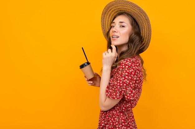 帽子と孤立したオレンジ色の背景に紙コップと赤いドレスのヨーロッパの魅力的なスタイリッシュな笑顔の女性のスタジオポートレート