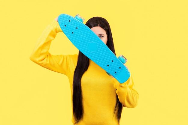 Студийный портрет девушки, закрывающей лицо скейтбордом, изображение на желтом фоне