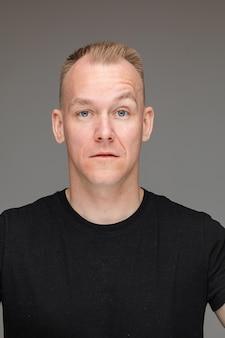 眉を上げてカメラを見て、自信と傲慢さを示す、黒いtシャツを着た短いブロンドの髪と青い目をしたハンサムな男性のスタジオポートレート。