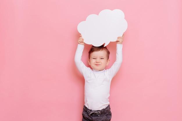 구름 모양의 깨끗한 화이트 보드를 가진 행복한 소년의 스튜디오 초상화