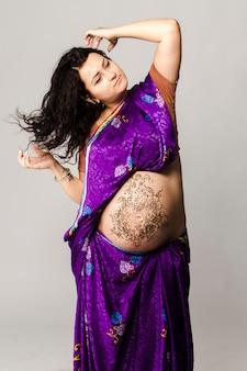 Студийный портрет счастливой беременной женщины в индийском сари, расписанный хной беременный живот