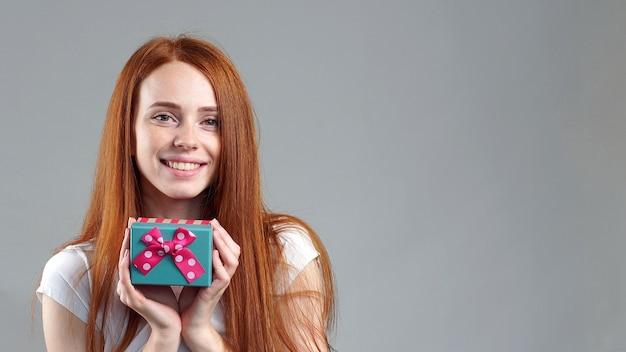 Студийный портрет красивой рыжей девушки с небольшой подарочной коробкой
