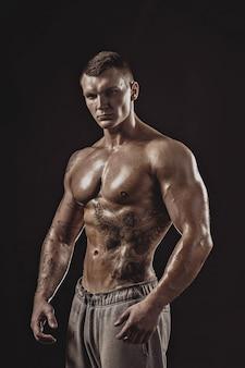 上半身裸の運動入れ墨の男のスタジオポートレート