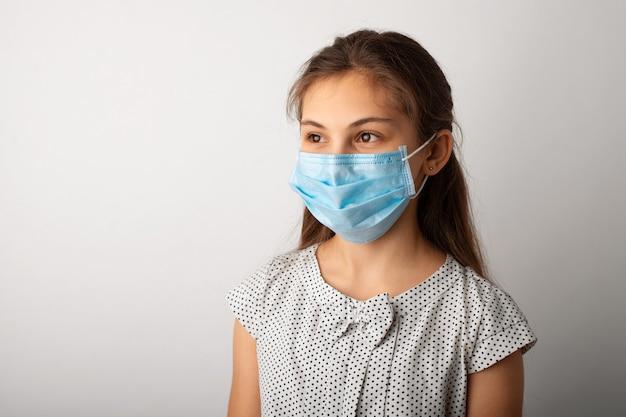 Студийный портрет маленькой девочки в медицинской маске и перчатках