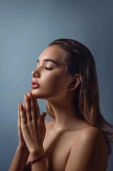 Студийный портрет женщины со сложенными руками как на молитве