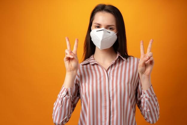 Студийный портрет молодой красивой женщины в медицинской маске на желтом фоне Premium Фотографии