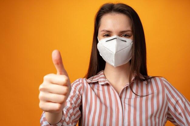 Студийный портрет молодой красивой женщины в медицинской маске на желтом фоне