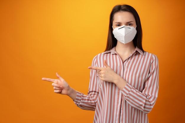 Студийный портрет молодой красивой женщины в медицинской маске против желтого