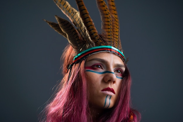 Студийный портрет молодой девушки с коренным макияжем и аксессуарами