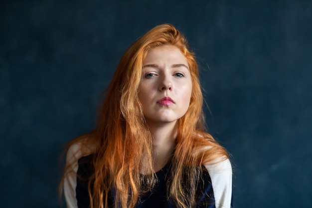 若い赤毛の美しい少女のスタジオポートレート。青い背景の上の女性の感情。感情の地図。