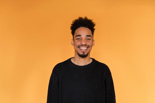 オレンジ色の壁に笑みを浮かべて黒のプルオーバーを着ているアフロアメリカンの男のスタジオポートレート。