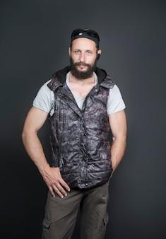キャップ、サングラス、フーディベストとジーンズ、アーバンスタイルまたはスポーツカジュアルを身に着けているアメリカのハンサムなひげを生やした男のスタジオポートレート。ポケットに手を入れて、フード付きのオープンベストを着た深刻なロシア人