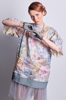 Студийный портрет привлекательной европейской модели в ярком пальто и прозрачной юбке