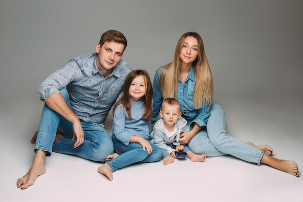 裸足で床に座ってカメラに微笑んでいるデニムの衣装で赤ちゃんの息子と魅力的な母親、ハンサムな父と素敵な娘のスタジオポートレート。